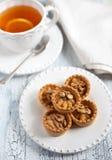 Tee und Törtchen mit Buttersahne und -walnüssen Stockbild