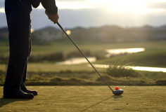 Tee up 01. A right handed golfer tees off in the early morning light Stock Photos