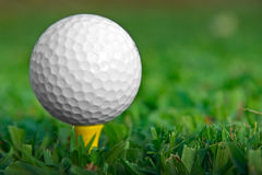 Tee up horizontal. Golfball on yellow tee Royalty Free Stock Photography