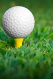 Tee up vertical. Golfball on yellow tee Royalty Free Stock Photos