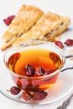 Tee von einem dogrose mit Stück des Kuchens Stockfotografie