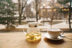 Tee von einem Sanddorn in einer transparenten Teekanne auf einem Holztisch auf einem Fenster, welches die Straße gegenüberstellt Stockfotografie