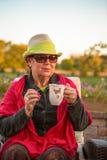 Tee-Zeit, warme, ältere Dame mit ihrem heißen Tee zu bleiben Stockfotografie