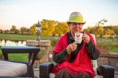 Tee-Zeit, warme, ältere Dame mit ihrem heißen Tee zu bleiben Stockfoto