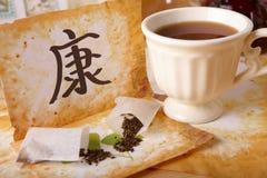 Tee zerstreute, chinesisches Gesundheitssymbol und Teecup Stockfotos