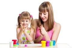 Teeaching κόρη μητέρων για να χρησιμοποιήσει το ζωηρόχρωμο άργιλο παιχνιδιού στοκ εικόνα