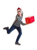 Teeager dans le chapeau de Santa fonctionnant avec un cadeau Images stock