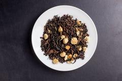 Teeasiat blüht oolong auf weißer Platte auf dunklem backgroung Lizenzfreies Stockfoto