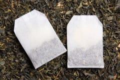 Teebeutel über getrocknetem Teeblatthintergrund Stockbilder
