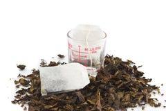 Teebeutel über getrocknetem Teeblatthintergrund Stockfotos