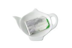 Teebeutel auf Teekanne geformtem Saucer Stockbild