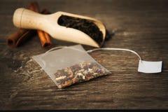 Teebeutel und eine Schaufel mit Tee auf einem hölzernen Hintergrund lizenzfreie stockbilder