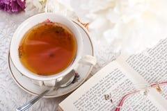 Teecup, das Buch und Gläser Stockfotografie