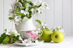 Teecup mit Blumenblüten und grünen Äpfeln Stockfoto