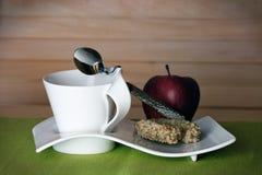 Teecup mit einem Apfel und einem Plätzchen Stockbild