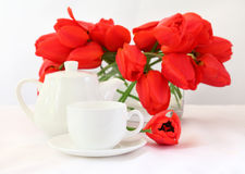 Teecup und rote Tulpen Stockbild