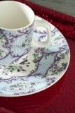 Teecup und -teller der England-alten Art über rotem Tellersegment Stockfotos