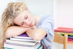 Teeenager cansado que duerme en una biblioteca Foto de archivo