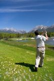 Teeing Off. A golfer tees off in the Rocky Mountains stock photo