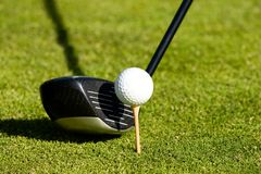 Teeing off. Golf club next to a ball on a tee Stock Photo