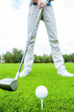 Teeing off. Close-up of golfer teeing off while standing on golf course royalty free stock image