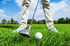 Teeing off. Close-up of male golfer teeing off while standing on golf course stock photo