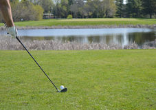 Golfer Teeing off in front of a Water trap royalty free stock image