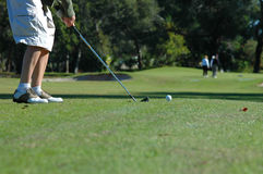 Teeing up. At a short par 3 - or a woman about to take a shot on the golf course Stock Photo