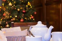 Teekanne, Becher, Zucker, Korb, Serviette, Weihnachtsbaum Stockfotografie