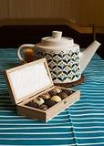 Teekanne, Kerze und eine Holzkiste Pralinen Stockfotografie