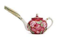 Teekanne mit dem Dollarschein, der aus Tülle heraus haftet Lizenzfreies Stockfoto