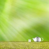 Teekanne mit nettem grünem Hintergrund Stockfotografie