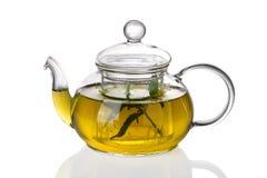 Teekanne mit Tee und frischen Blättern Lizenzfreies Stockfoto