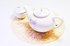Teekanne und Cup auf der Matte Lizenzfreie Stockfotografie