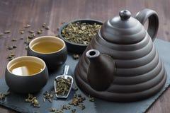Teekanne und Cup mit grünem Tee Stockbild