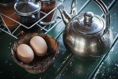 Teekanne und Ei in der hölzernen Schale Stockfotografie