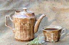Teekanne und ein Becher mit Tee auf Leinwand lizenzfreie stockbilder