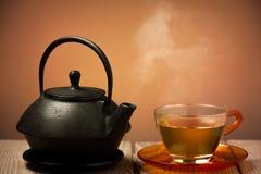 Teekanne und eine Tasse Tee Stockbild