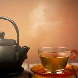 Teekanne und eine Tasse Tee auf einer alten hölzernen Tabelle - heißes Dampf smoki Stockfoto