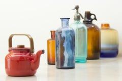 Teekanne und Flaschen über weißem Hintergrund lizenzfreie stockfotos