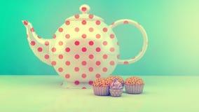 Teekanne und kleine Kuchen Stockbilder