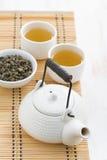Teekanne und Schalen grüner Tee auf einer Weidenmatte, Draufsicht Lizenzfreie Stockfotografie