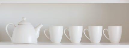 Teekanne und Schalen im Regal Stockbild