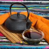 Teekanne und Tasse Tee auf dem ethnischen Hintergrund von einem gestreiften Lizenzfreie Stockfotos