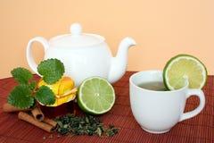 Teekanne und Tasse Tee mit Kalk Stockbild