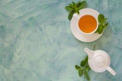 Teekonzept Teekanne und Schale mit grünem Kräutertee verzierten tadellose Blätter auf hölzernem Hintergrund stockfotografie