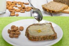 Teelöffel mit Honig über Brot mit Mandel-Butter und Milch lizenzfreies stockfoto