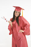 Beautiful Caucasian woman wearing a red graduation gown holding diploma Royalty Free Stock Image