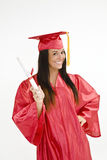 Beautiful Caucasian woman wearing a red graduation gown holding diploma Stock Image