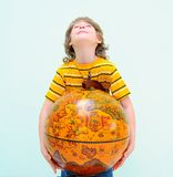 Teen. Hugging Old Fashioned Globe Against Light Green Background Royalty Free Stock Image